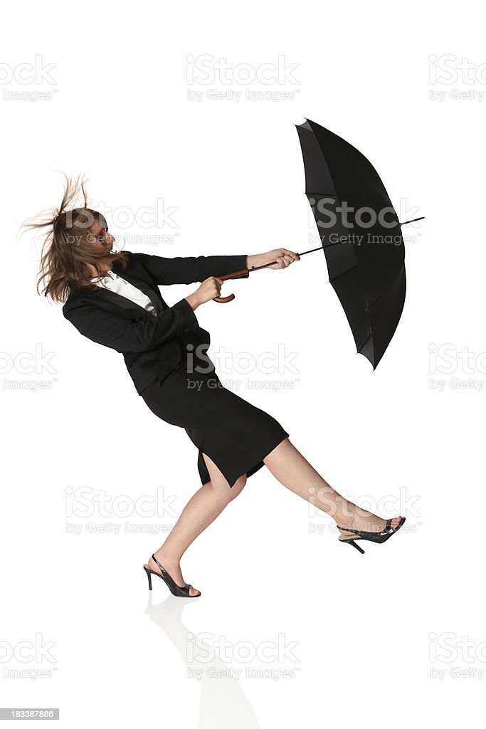 Isolated businesswoman blowing away with umbrella royalty-free stock photo