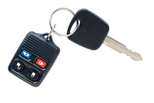 Isolated car key and remote.  A car key and remote door locking device on a simple keyring, isolated on white. car key stock pictures, royalty-free photos & images