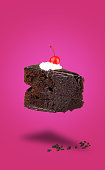 istock Isolated chocolate cherry cake flying on pink background 620712368