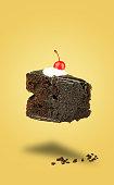 istock Isolated chocolate cherry cake flying on yellow background 620712394