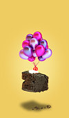 istock Isolated chocolate cherry cake with balloons on yellow background 1070843742