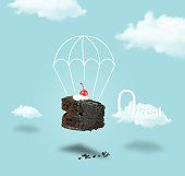 istock Isolated Chocolate cherry cake with parachute on blue sky background 620979728