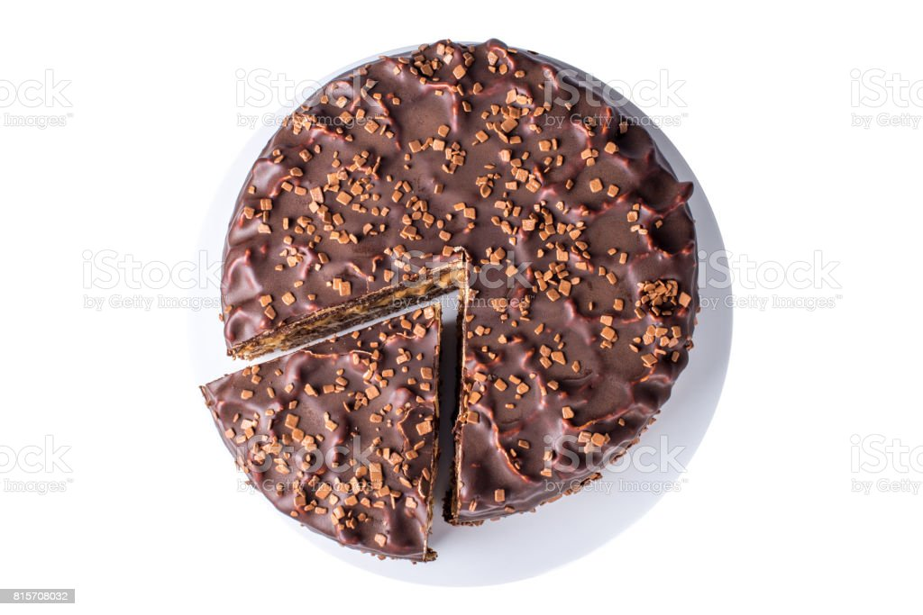 isolated chocolate layered cake with nougat and sponge cake in the cut on the plate, top view stock photo