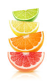 Isolated citrus fruits wedges. Pieces of grapefruit, orange, lemon and lime on top of each other isolated on white background with clipping path