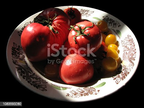 Isolated dish with ripe homemade red and yellow tomatoes on a black background in bright light