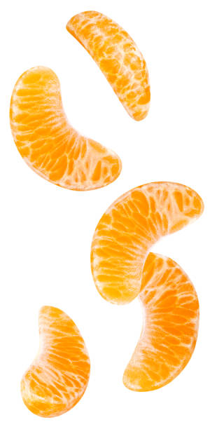 Isolated falling orange segments. Isolated falling orange segments. Five peeled pieces of orange or tangerine fruit in the air isolated on white background with clipping path tangerine stock pictures, royalty-free photos & images