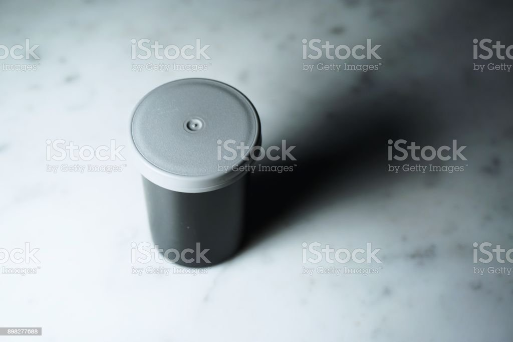 Isolated film canister on white marble stock photo