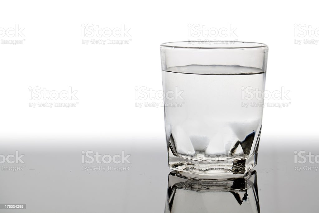 Isolated glass of water on the table with reflection stock photo