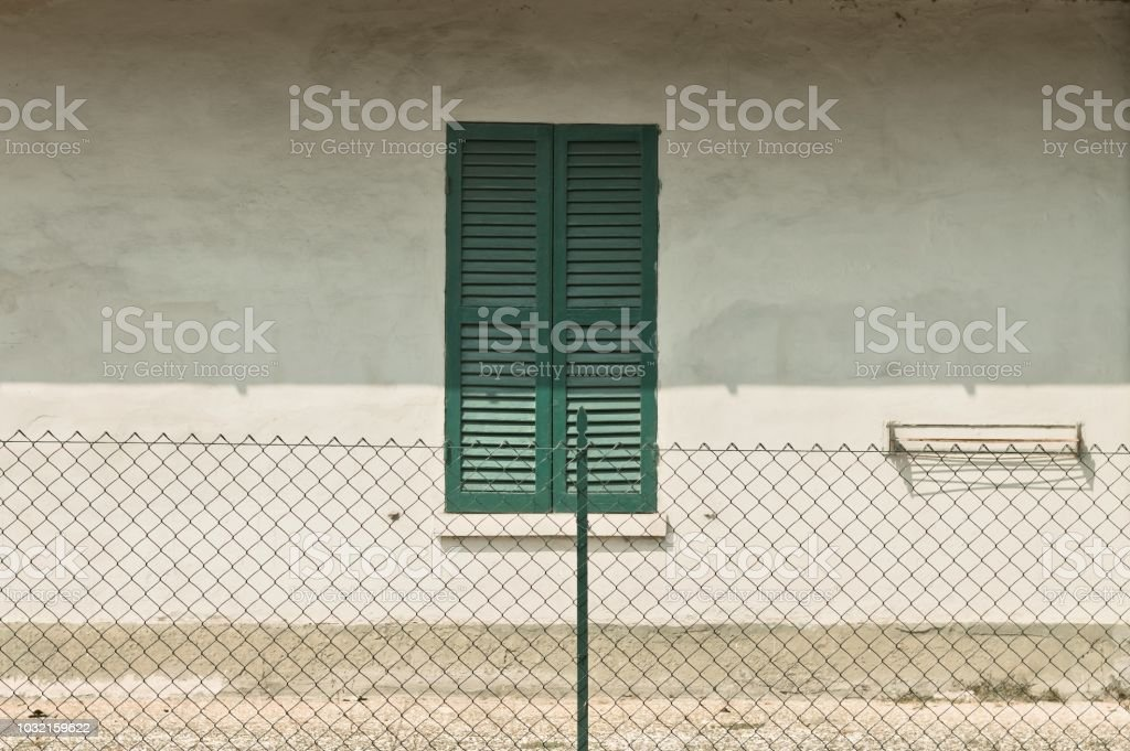 Isolated green window behind a fence (Pesaro, Italy, Europe) stock photo