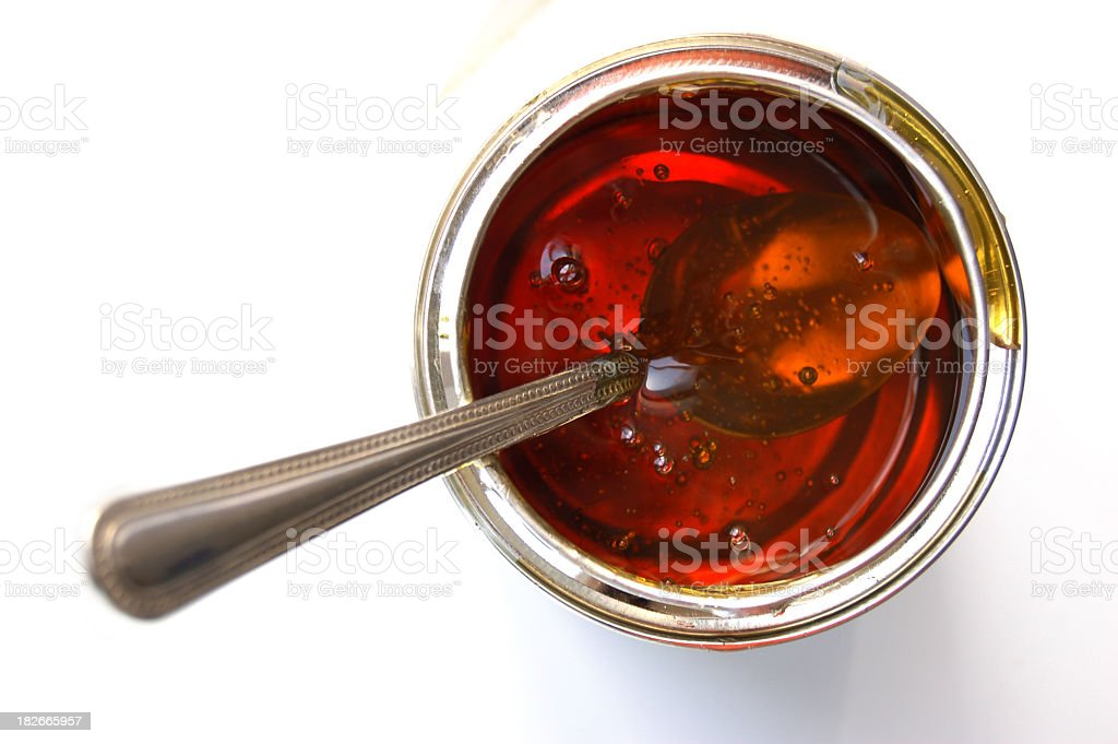 Isolated image of a spoon inside a jar of syrup stock photo