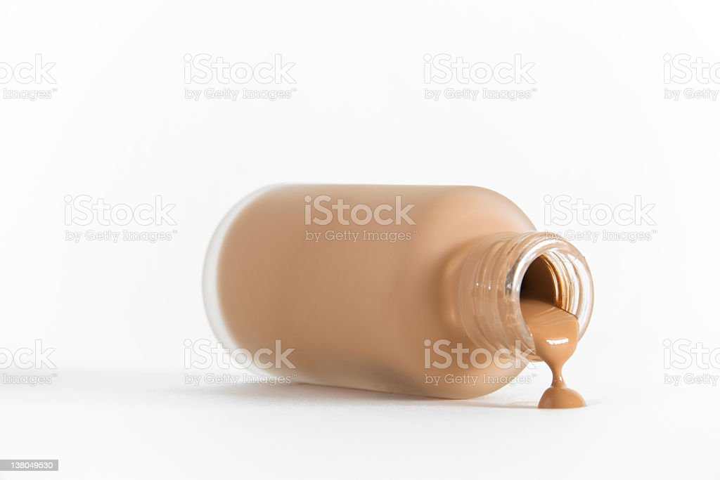 Isolated image of bottle of make-up on its side pouring out stock photo