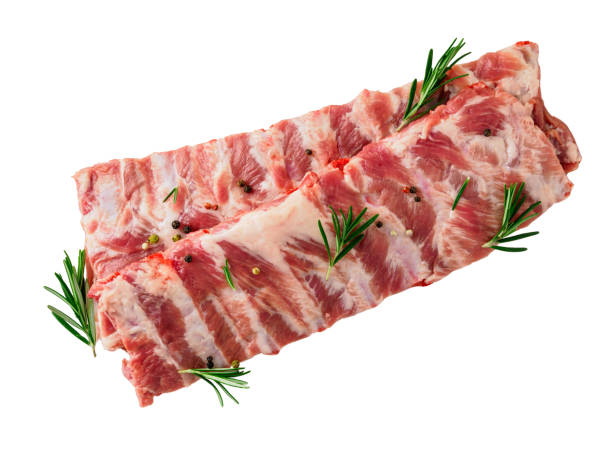 Isolated image of raw pork ribs with seasoning  rosemary, pepper on white background, top view Isolated image of raw pork ribs with seasoning  rosemary, pepper on white background, top view pork stock pictures, royalty-free photos & images