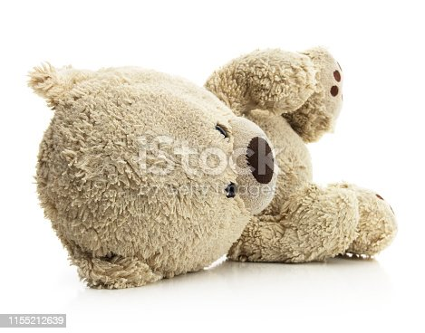Isolated fallen teddy bear on a white background.