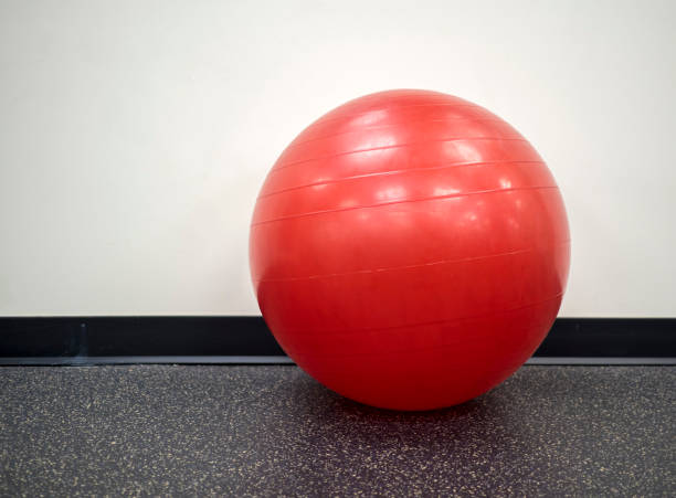 Isolated lone red exercise ball in the gym stock photo