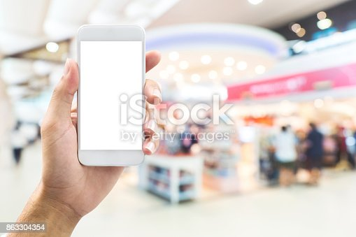istock isolated man hand holding smart phone over abstract blurred background with bokeh in shopping mall, department store 863304354
