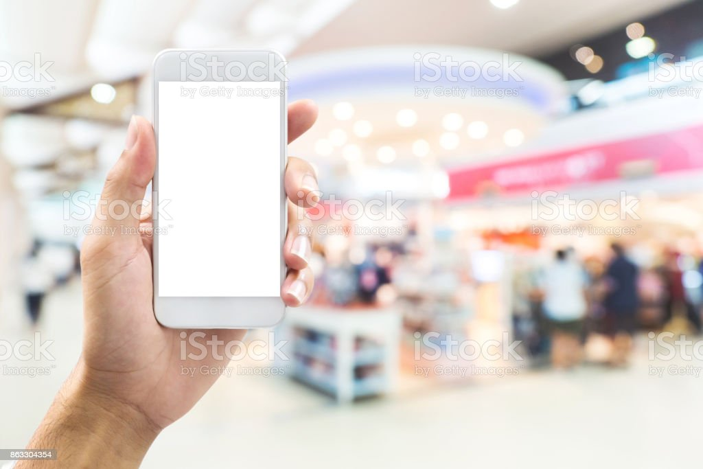 isolated man hand holding smart phone over abstract blurred background with bokeh in shopping mall, department store stock photo