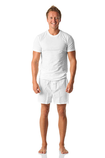Isolated man standing in white shirt and boxers stock photo