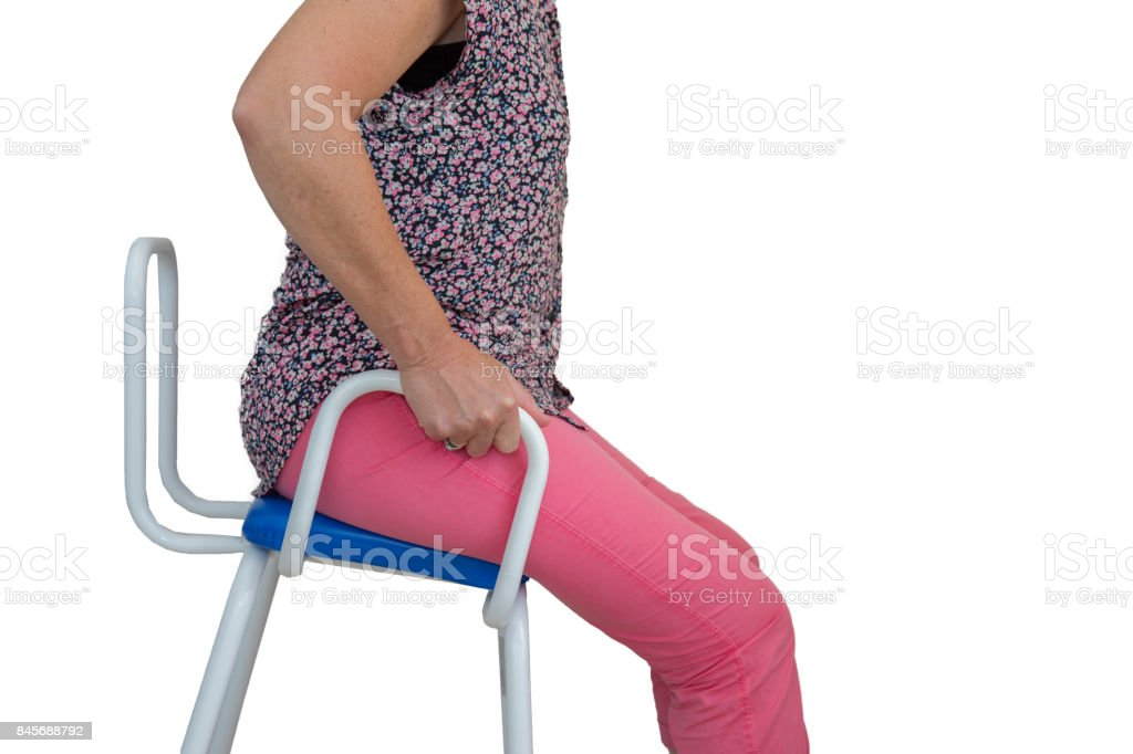 Isolated - middle aged woman using a perching stool stock photo