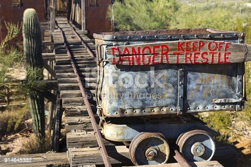 Isolated Mine Cart with Red Paint Danger Trestle Sign on Old Rusted Rail Tracks next to Saguaro Cactus in Arizona Desert near Phoenix