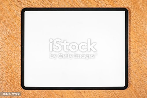 istock Isolated modern tablet computer on a wooden bench 1069772868