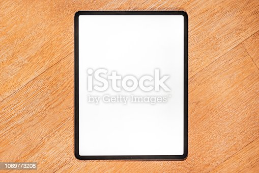 istock Isolated modern tablet computer on a wooden bench 1069773208