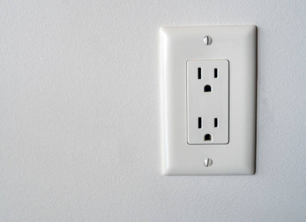 Isolated North American power outlet plug in socket on a white wall background Type B style stock photo
