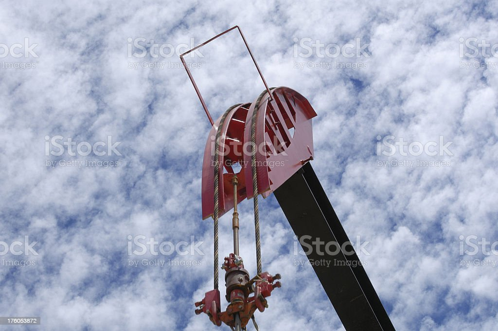 Isolated Oil Pumpjack Pulley with Clouds in Background stock photo