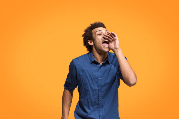 Isolated on blue young casual man shouting at studio Young afro man shouting. Crying emotional man screaming on blue studio background. Male half-length profile portrait. Human emotions, facial expression concept. Trendy colors. crying stock pictures, royalty-free photos & images