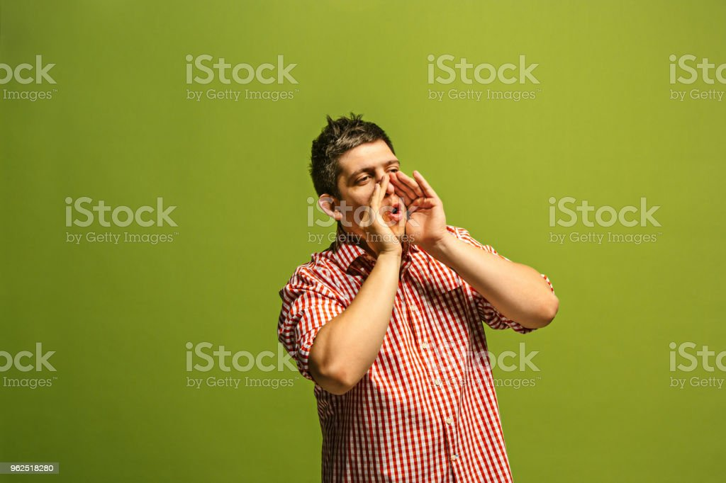 Isolated on green young casual man shouting at studio - Royalty-free Adult Stock Photo