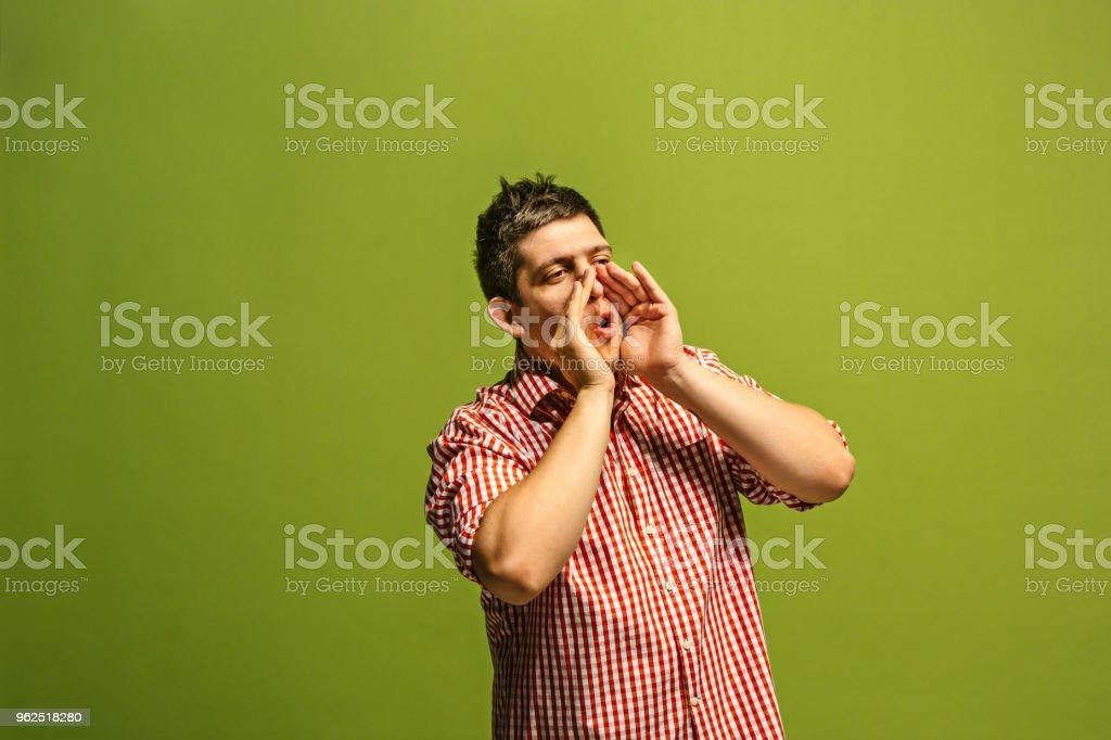Isoladas em verde jovem casual gritando no estúdio - Foto de stock de Aberto royalty-free
