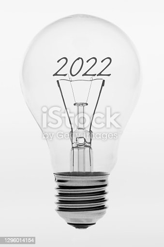 istock Isolated photo of an old-fashioned glass light bulb with the text two thousand and twenty two 1296014154