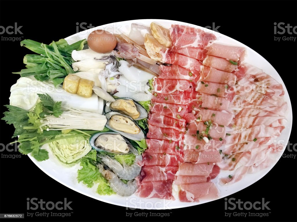 isolated photography on black background with clipping path of mix Pork slice and seafood platter set served on big white plate dish top with rich soya sauce for Shabu or Sukiyaki Japanese hot pot style stock photo