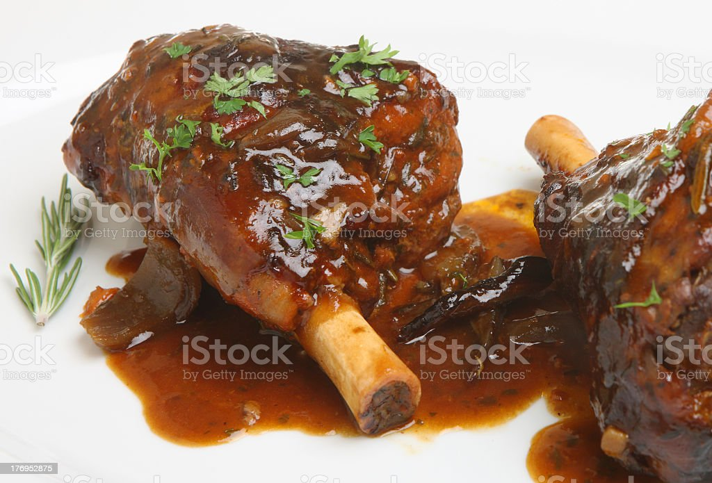 Isolated picture of roasted lamb shanks stock photo