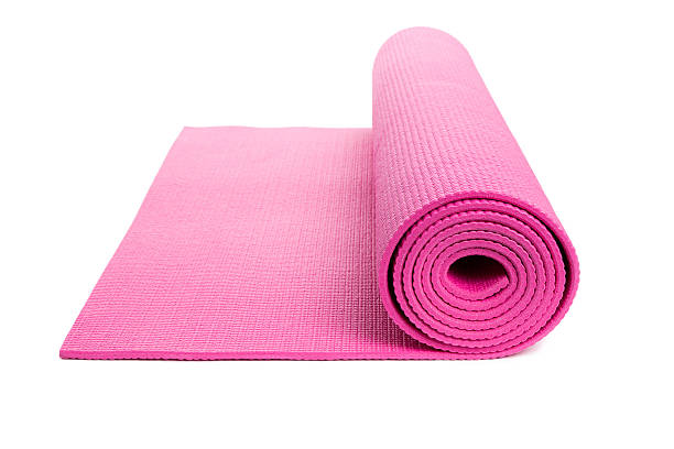 Isolated pink yoga mat, slightly unrolled stock photo