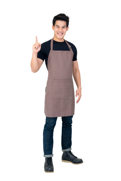 Isolated portrait of a young attractive male asian barista Isolated portrait of a young attractive male asian barista in brown apron smiling and  pointing hand upward apron stock pictures, royalty-free photos & images