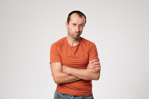 istock Isolated portrait of angry man wearing orange t-shirt holding arms crossed, having skeptical and dissatisfied look. 862465002