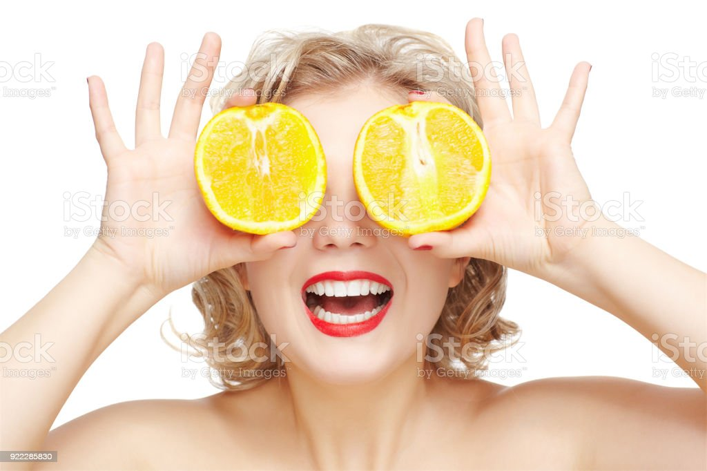 isolated portrait of beautiful happy young blonde size plus woman model closing her eyes with halfs of orange stock photo