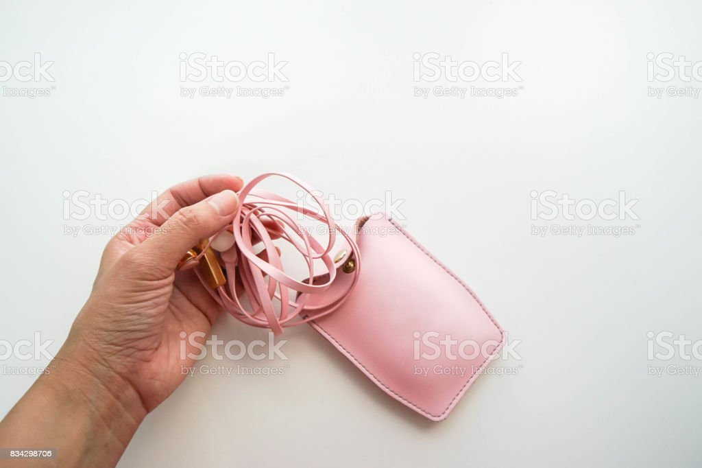 isolated pull pink cute earphone from leather case for listening to music stock photo