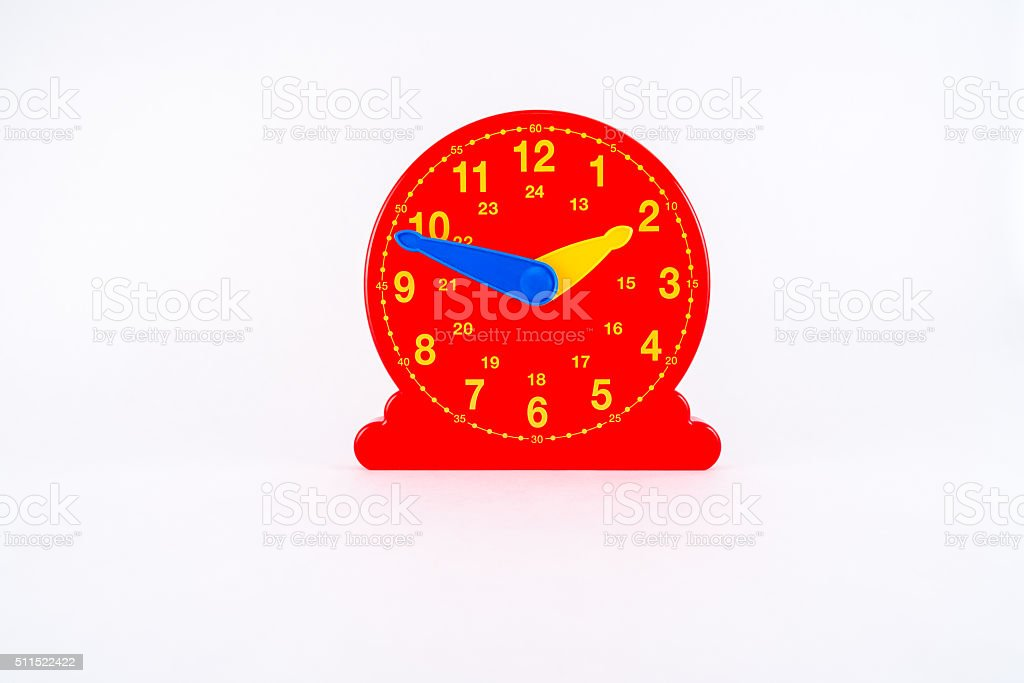 Isolated red plastic clock toy for learning time. stock photo