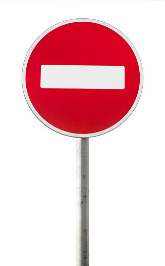 Round red road sign on metal pole. No Entry road-sign mounted on urban roadside