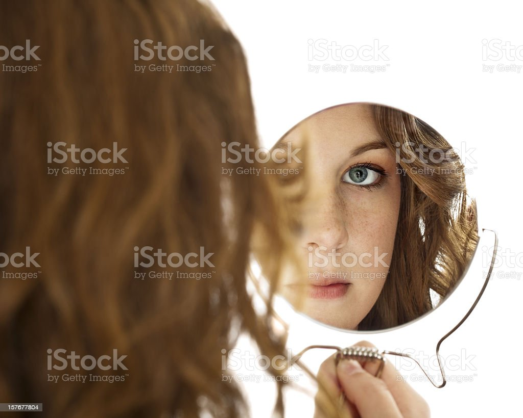 Isolated Reflection of Female Brunette Teen Gazing Into Handheld Mirror royalty-free stock photo