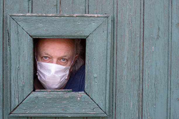Isolated senior behind old door, wearing mask stock photo