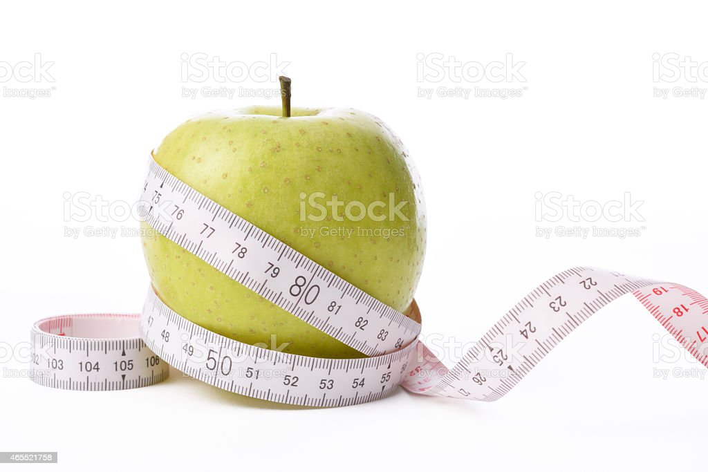 Isolated shot of apple with measurement tape on white background stock photo