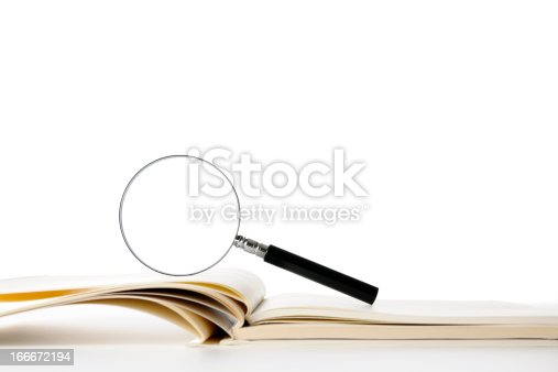 istock Isolated shot of blank book with magnifying glass on white 166672194