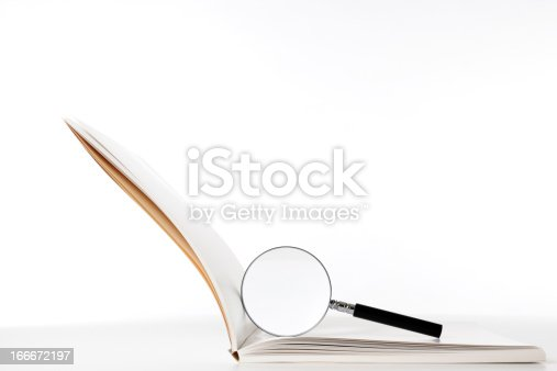 istock Isolated shot of blank book with magnifying glass on white 166672197