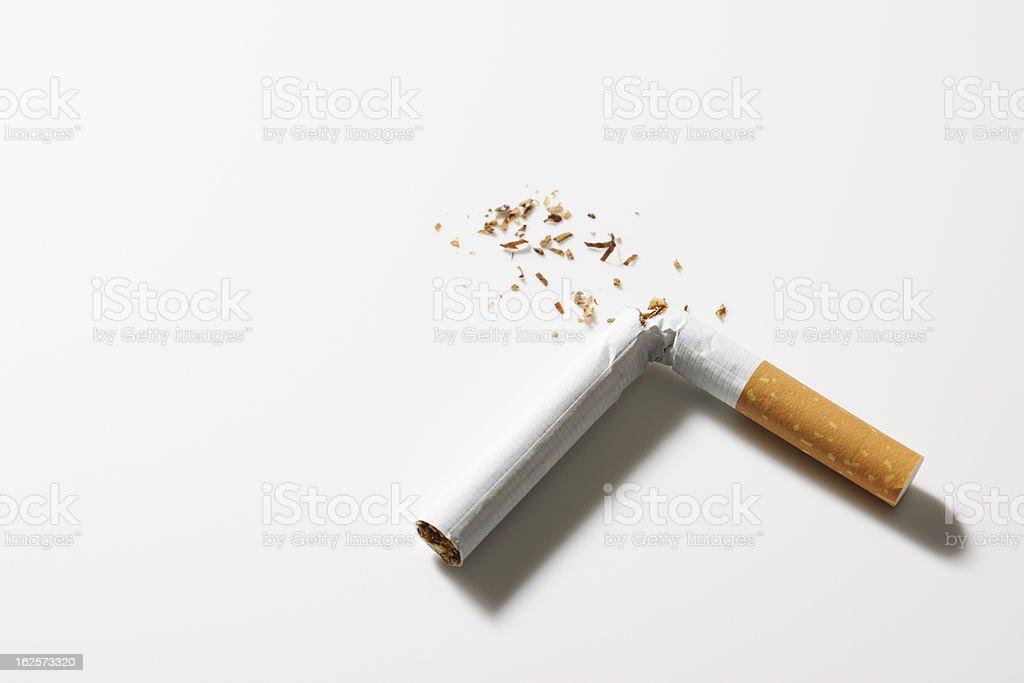Isolated shot of broken cigarette on white background stock photo