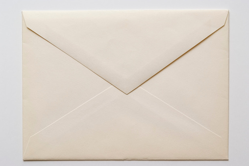 Close-up shot of closed an old envelope isolated on white background.