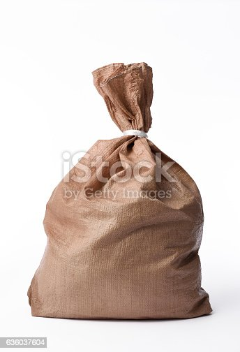 istock Isolated shot of closed brown garbage bag on white background 636037604