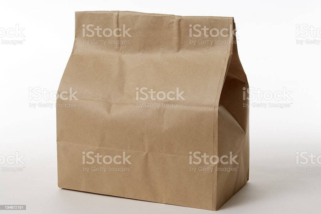 Isolated shot of closed brown paper bag on white background stock photo