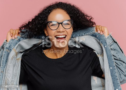 Isolated shot of curly cheerful woman tries on new denim jacket, wears optical glasses, smiles broadly, has perfect mood, poses against pink wall. Positive emotions. Afro female in stylish clothes